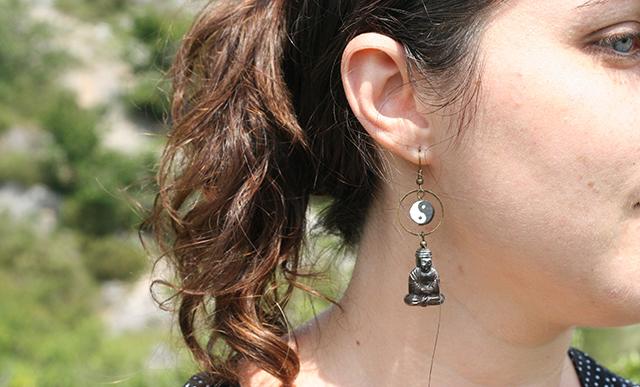 Boucles d'oreilles fantaisie zen avec une perle bouddha et une perle représentant le yin et le yang.
