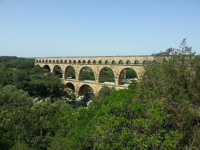 Vue sur le pont du Gard à travers les arbres.