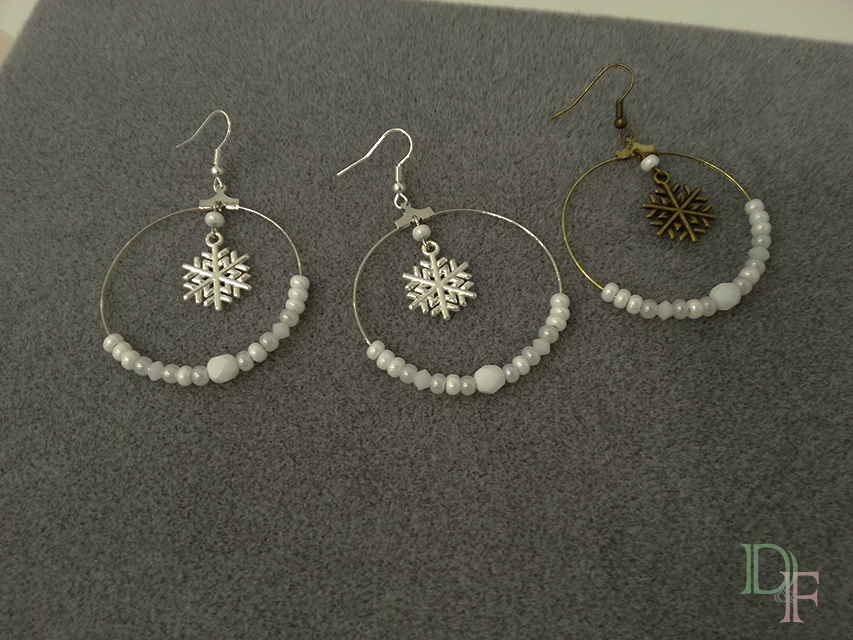 Boucles d'oreilles façon créoles argentées avec flocons de neige et perles blanches.